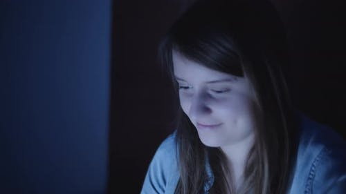 Woman in denim jacket at night