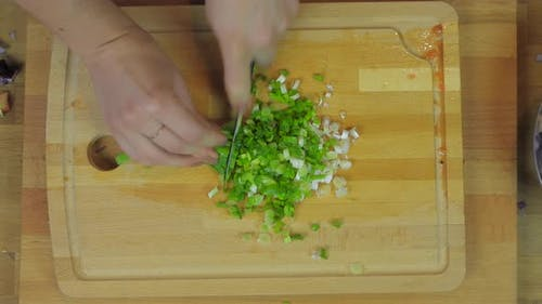 Woman Chopping Purple Onion, Lettuce, Parsley at Wooden Kitchen Table