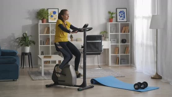 Fulllength Shot of Living Room with Sport Equipment Young Woman Is Training on Exercise Bike Workout