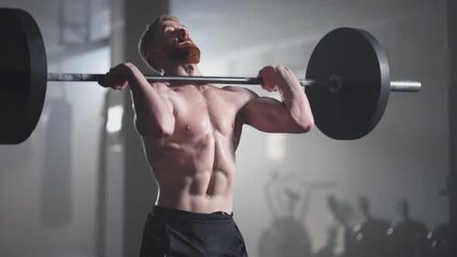 Athletic Beautiful Man Does Overhead Deadlift with a Barbell in the Gym