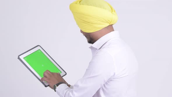 Thumbnail for Rear View of Bearded Indian Sikh Businessman Using Digital Tablet