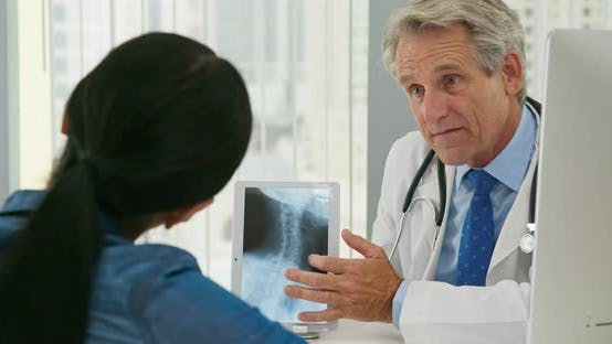 Woman listening to her health care provider explain spinal treatment with x-ray