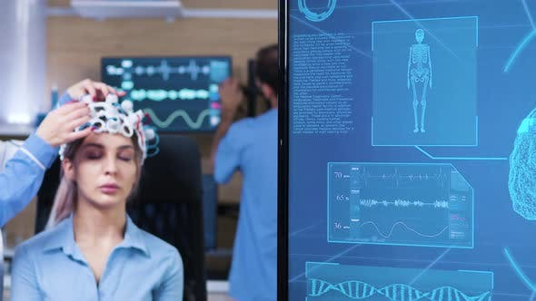 Cover Image for Female Doctor in Neuro Science Making Adjustments on Patient Headset