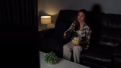 funny young woman watching TV on sofa at night