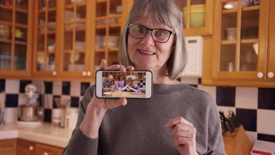 Thumbnail for Happy white grandmother showing off video of family on mobile device in kitchen