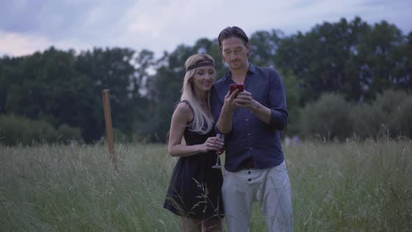 Thumbnail for Positive Couple Standing on Windy Summer Meadow in the Evening and Using Smartphone. Portrait of