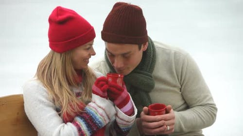 Couple drinking hot beverages at ice skating rink