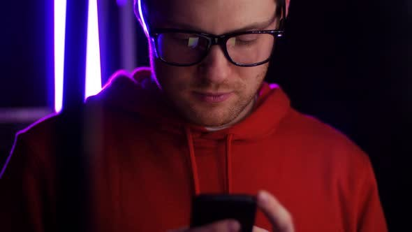 Cover Image for Young Man in Glasses with Smartphone in Dark Room 31