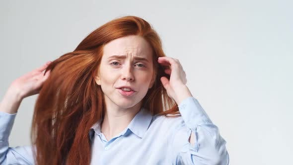 Thumbnail for Cheerful Young Redhead Girl Dancing and Looking at Camera on White Background