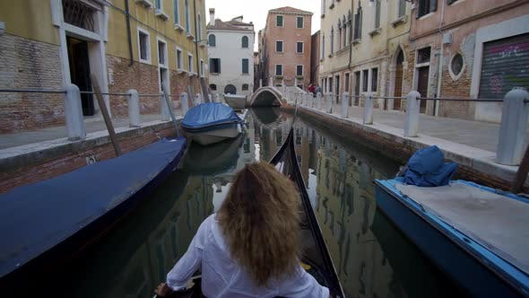 Cover Image for Young Woman in a Gondola Sails Under a Bridge in Venice