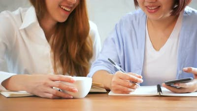 Asian women using phone and cup of coffee. Freelancer working in coffee shop.
