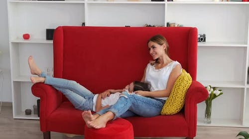 Mother and Daughter Lying on Red Couch in Living Room