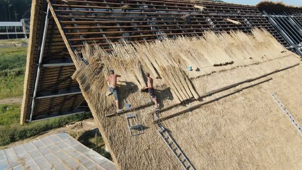 Thumbnail for Aerial View the Roof of a Large House with Dry Straw and Hay. Workers Who Install the Roof.