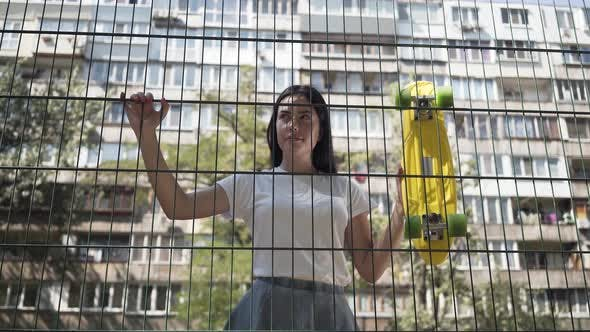 Portrait of Cute Woman with a Skateboard Looking at the Camera Standing Behind the Mesh Fence