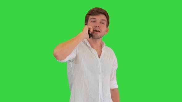Happy Young Man Talking on Mobile Phone and Smiling on a Green Screen, Chroma Key.