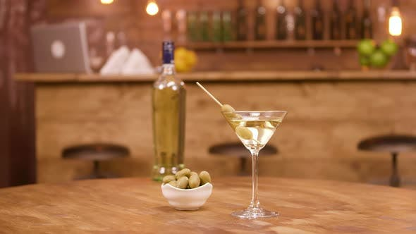 Thumbnail for A Bottle and a Glass of Martini with Olives on a Wooden Table