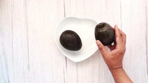 Hand Pick Avocado From a Plate on Wooden Table