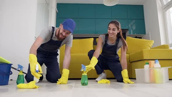 Thumbnail for Cheerful Young Man and Woman of the Cleaning Service Spraying Detergents and Wipping the Floor