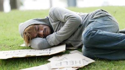 Beggar man lying on grass