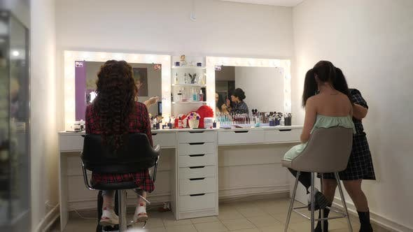 Easy Halloween Makeup. Girl in a Beauty Salon. Applying a Stylistic Pattern on the Face of the Model