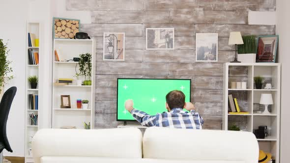 Thumbnail for Back View of Young Man Watching Sports on Tv