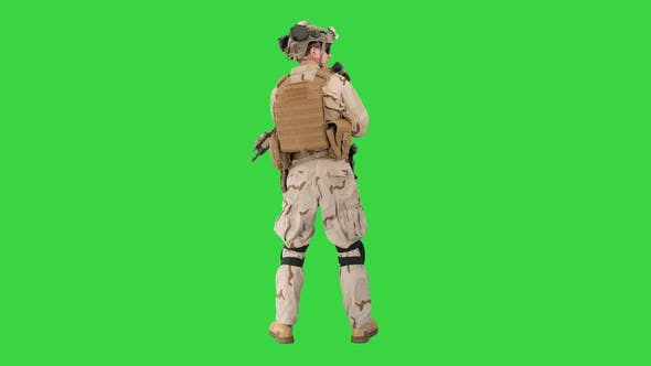 Fully Equipped Solder Holding Assault Rifle and Standing Looking To the Sides on a Green Screen