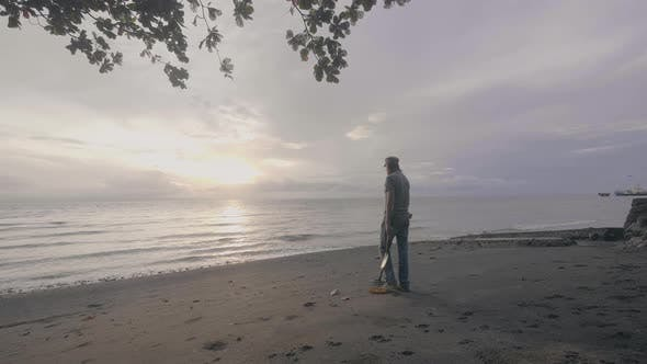 Thumbnail for Man Treasure Hunter with a Metal Detector Works on the Ocean Sand Beach at Sunset.