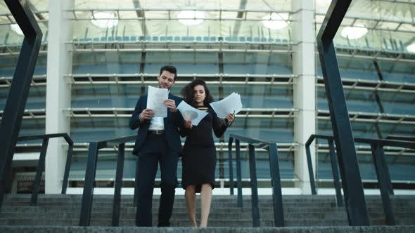 Thumbnail for Business Couple Walking with Documents. Couple Discussing Business Papers