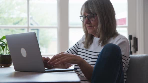 Thumbnail for Senior Caucasian woman working on laptop computer at dining room table