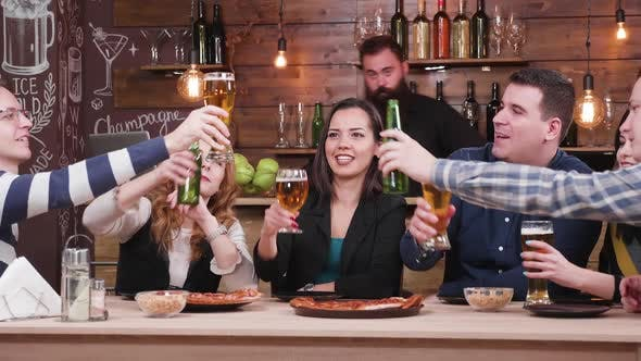 Thumbnail for Group of Friends Clinking Their Beers in Stylish Pub or Restaurant