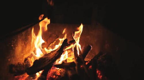 Beautiful Flames From Burning Slices Wood in Mangal at Night. Bonfire Inside Metal Brazier at