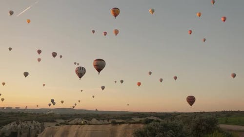 Aerial drone shot of hot air balloons soaring in the sky. Sunny morning in Cappadocia,