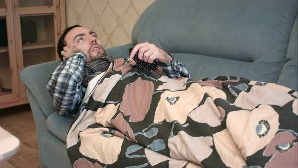 Cover Image for Unwell Man in Bed with Flu Calling Doctor on the Phone