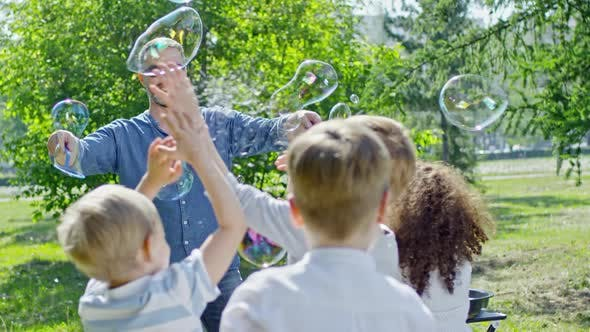 Thumbnail for Smiling Performer Making Soap Bubbles in Park