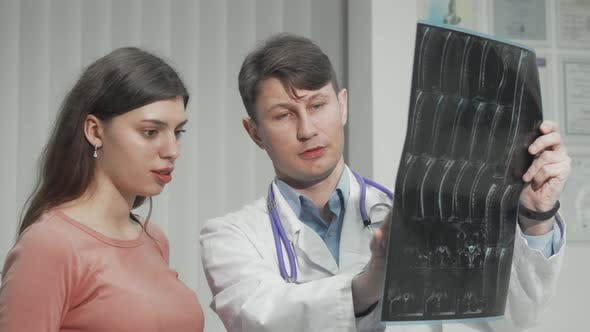 Male Doctor Explaining MRI Survey Results to His Female Patient