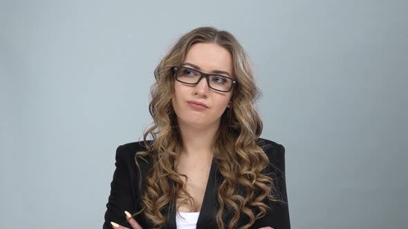 Thumbnail for Bussines Woman in Glasses Stands in Expectation at Grey Background, Slow Motion