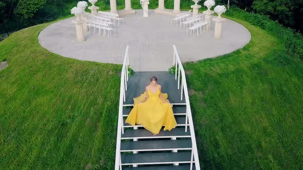 charming girl, in beautiful yellow fluttering dress, lit up by sun, rises up hill, up stairs