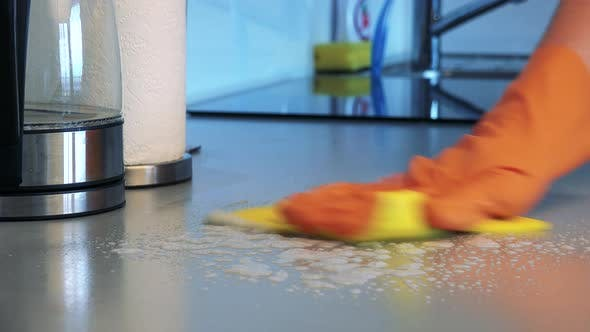 Thumbnail for A Man with Rubber Gloves Sprays a Detergent on the Kitchen Counter and Cleans It - Closeup