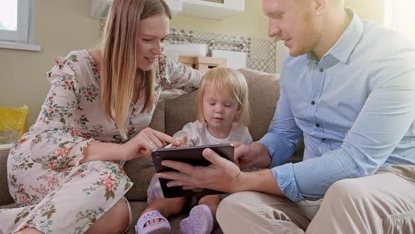 Thumbnail for Fröhlich kaukasischen Familie mit kleinen Mädchen sitzen auf dem Sofa, Lachen während beobachten etwas