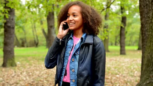 Thumbnail for Young African Chatty Smile Girl Talks with Friend Through the Smartphone in the Forest