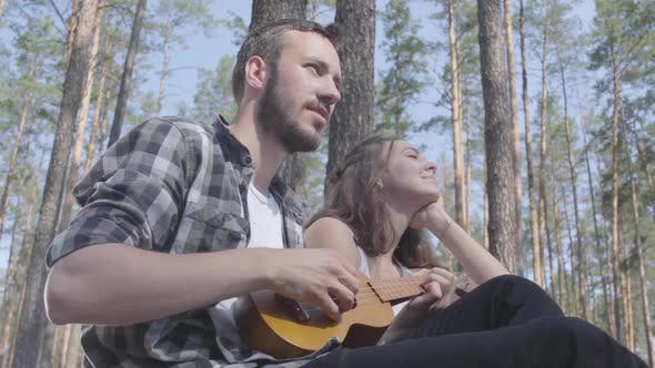Cover Image for Portrait Attractive Bearded Young Man Playing Ukulele While Pretty Young Happy Woman Sitting