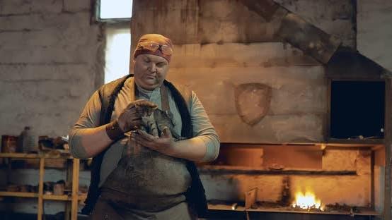 Brutal Blacksmith Holding a Kitten