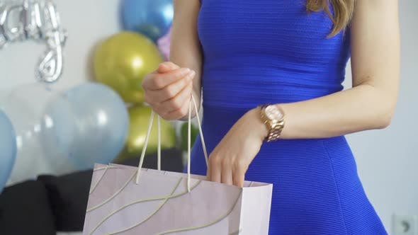 Close Up of Fit Woman in Blue Dress Reaching Into Birthday Gift Bag at Birthday Party
