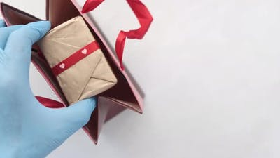 Hand in Latex Gloves Wapping a Gift Box with Tissue