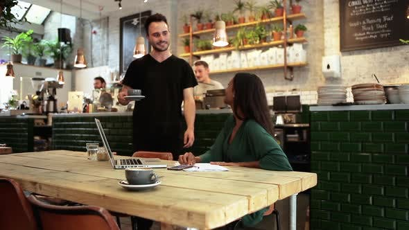Thumbnail for Man serving coffee to woman