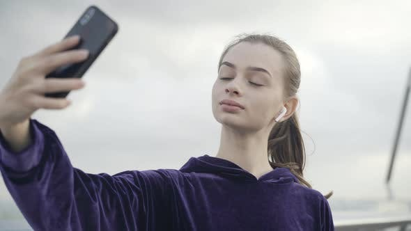 Closeup of Confident Beautiful Sportswoman Taking Selfie Outdoors on Cloudy Day