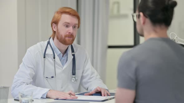 Redhead Male Doctor Giving Medical Report To Patient