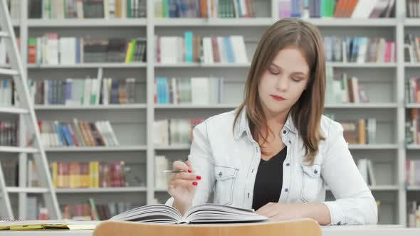 Female Student Writing in Her Textbook at Campus Library