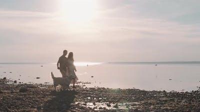 Couple Walking Dog by Seashore