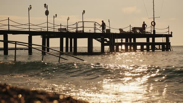 Cover Image for People Relax and Sunbathe on the Pier in the Early Morning